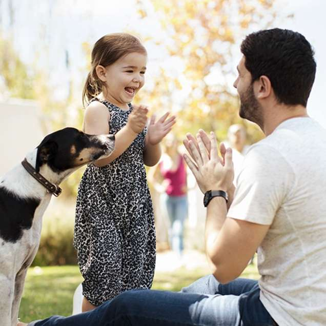Dad with daughter and dog on the lawn